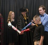 Young Recipients of 3-D Arms Surprise Manero at Commencement