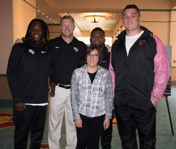 UCF Football's Shaquem Griffin, Coach Scott Frost, Mark Rucker and Aaron Evans with Dr. Annette Khaled at the AutoNation Cure Bowl Press Conference.