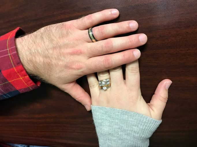 mans hand overlapping womans hand both with wedding rings