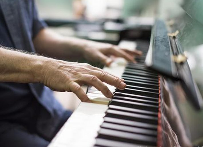 visual of mans hands playing piano