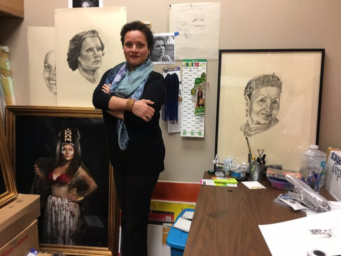 "Raimundi-Ortiz in her UCF studio, surrounded by her sketches and portraits of previous ""Reinas/Queens."""