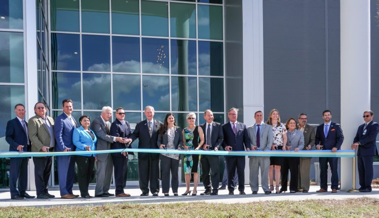 bridge ribbon cutting ceremony. group of men and women in suits standing in front of glass building, about to cut a long ribbon