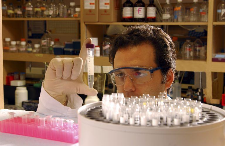 man with goggles in lab looking closely at test tube