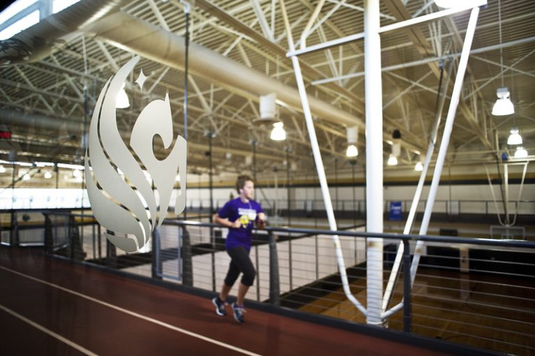student walking by pegasus logo at ucf recreation and wellness center