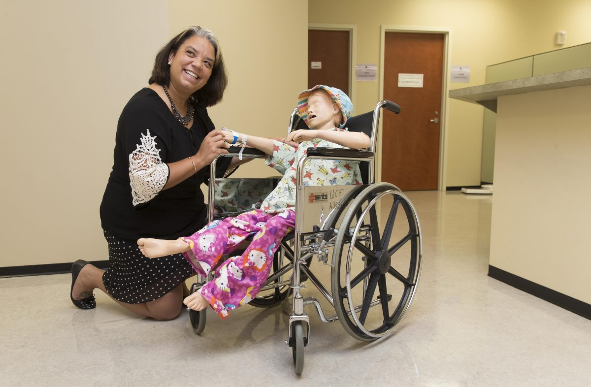 woman in a black dress with white sleeves kneels next to a mannequin in hospital scrubs sitting in a wheelchair