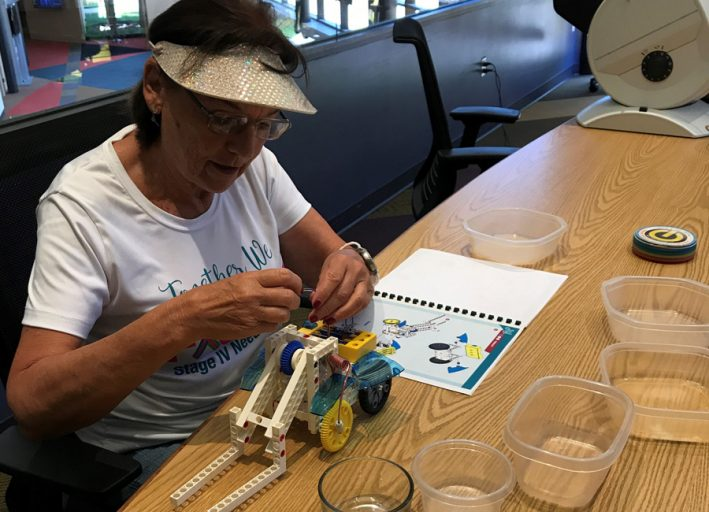 Volunteer Kathleen Sanborn assembles a robot kit using easier-to-understand picture instructions.