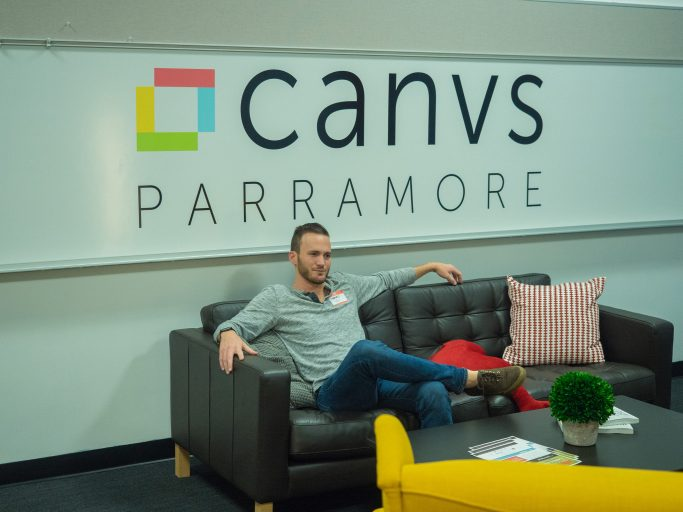 """man sitting on couch in front of banner that reads """"canvas PARRAMORE"""""""