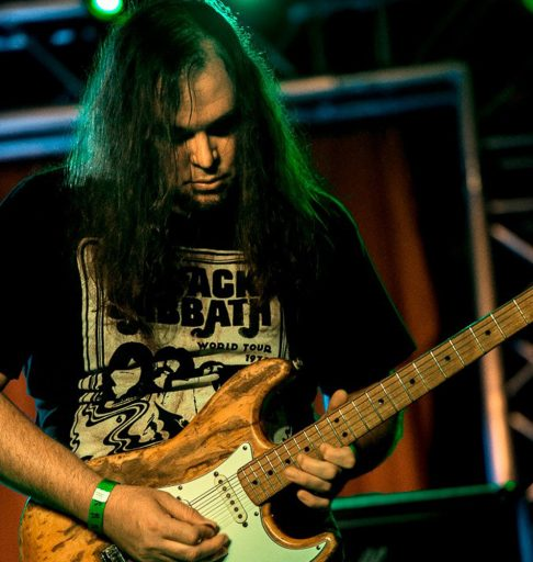 Professor Tommy Harrison playing electric guitar