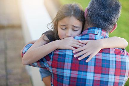 man in plaid shirt hugging distressed young girl with eyes closed