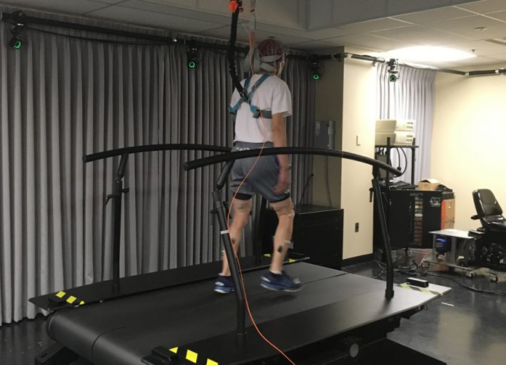 older male having an eeg performed while walking on treadmill