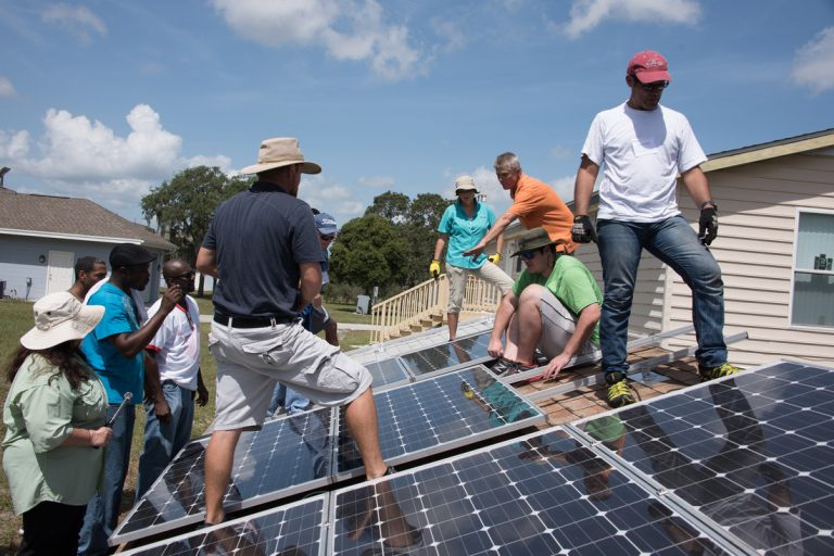 people working on solar panels