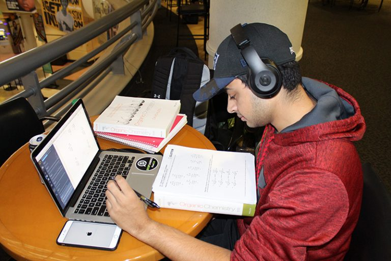 student with headphones on studying at student union table