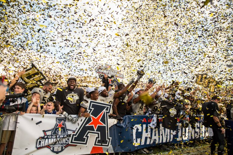 ucf football celebration with black, white, gold confetti falling from sky. banners held up.