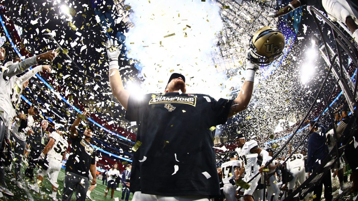 "White and gold confetti showers a player wearing a black ""Champions"" shirt as he holds his gold helmet and looks out at the crowd."