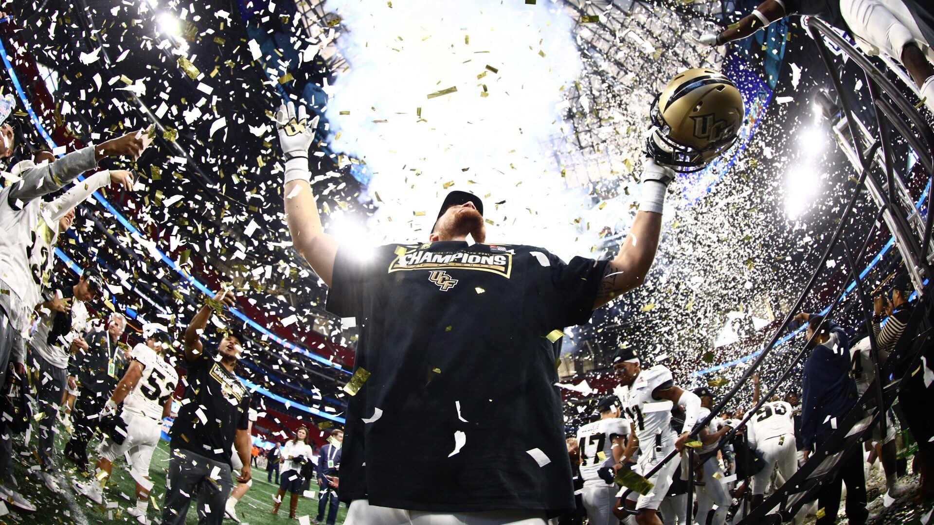"""White and gold confetti showers a player wearing a black """"Champions"""" shirt as he holds his gold helmet and looks out at the crowd."""