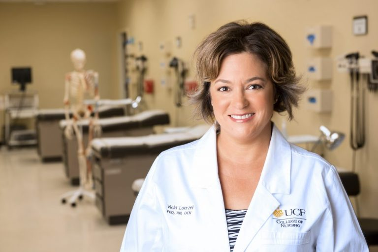 femal ucf doctor with short hair smiling in white lab coat, standing in front of patient beds with fake skeleton in background