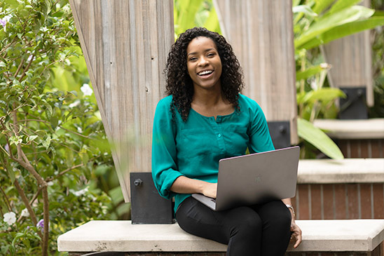 A smiling woman wearing a green top sits outside with a laptop.
