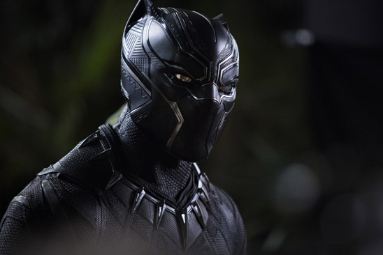 A man wears black costume that looks like a panther with claws around his neck.