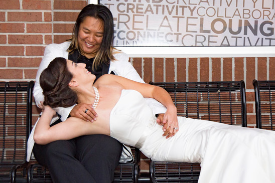 A woman in a wedding gown reclines in the lap of a woman in a black suit with a white jacket.