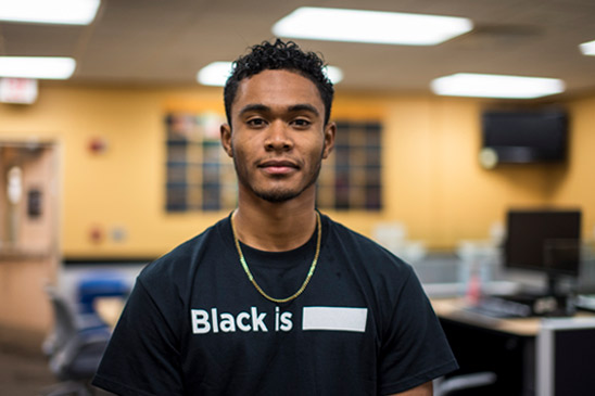 Travis Slocum wearing a black shirt with white text that reads Black Is ___.