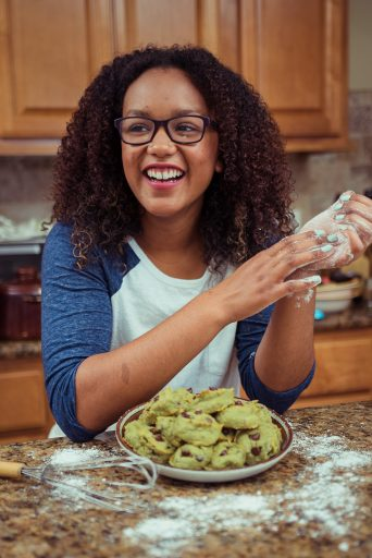 black student excited and smiling while baking cookies