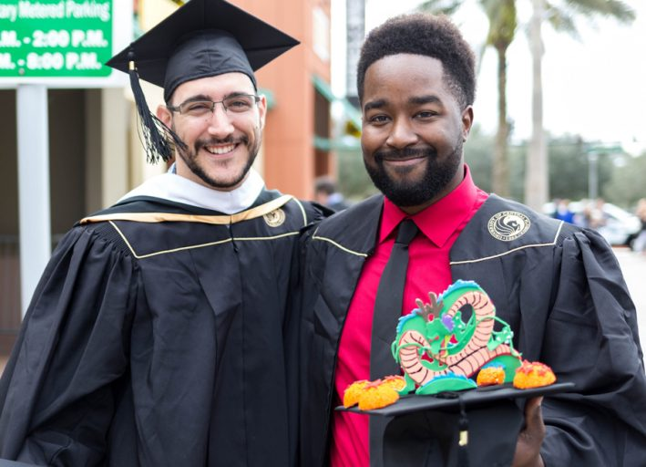 Two FIEA students in cap and gown at graduation