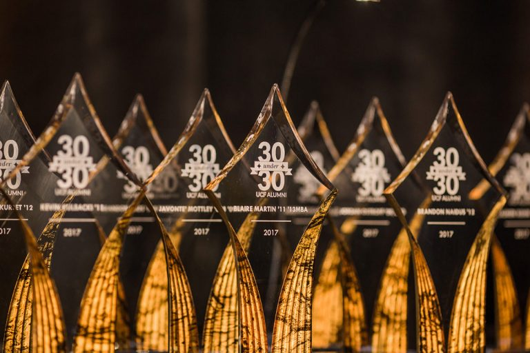 Nine glass awards in the shape of diamonds are in front of a black background and are backlit with yellowish orange color. The awards say 30 Under 30 in white text.