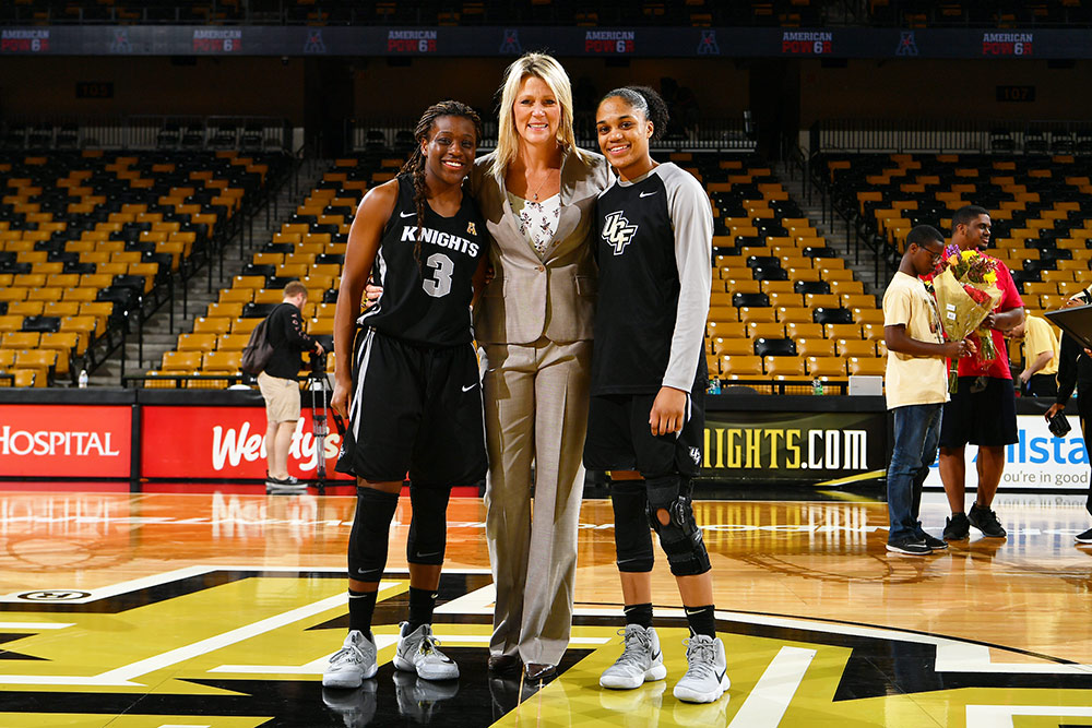 A white woman in a beige suit stands between two black players on a basketball court with empty seats in the background.
