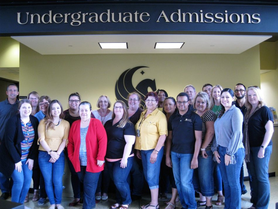 group of ucf's undergraduate admissions staff standing in front of pegasus logo and below a black sign with gold lettering 'undergraduate admissions'