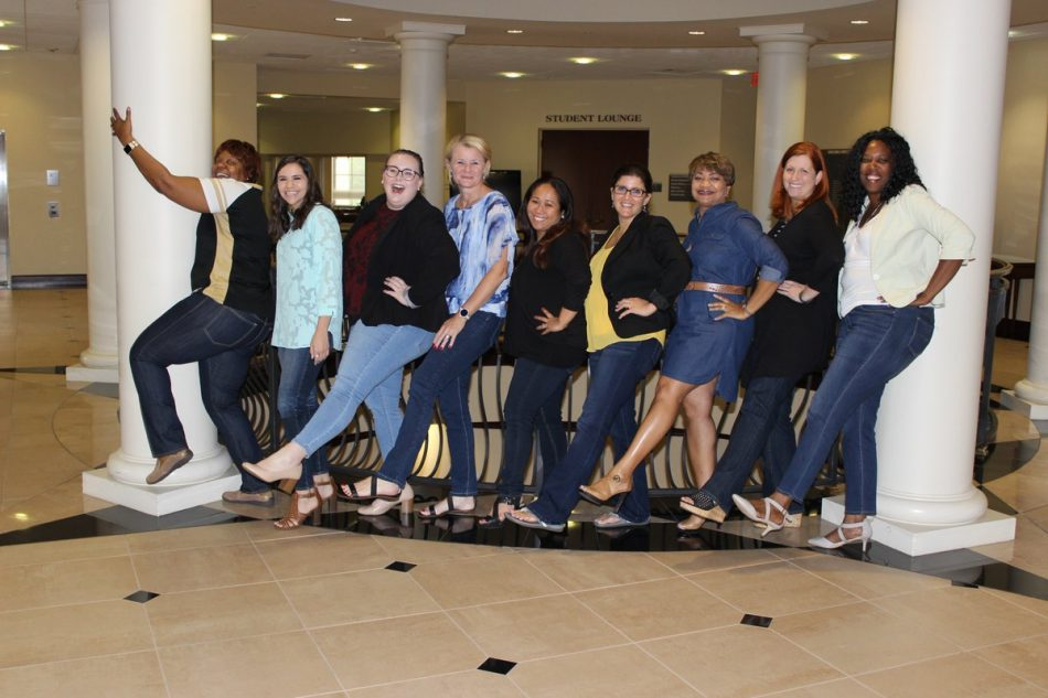group of ucf staff From the Rosen College of Hospitality Management all facing to the left and kicking their left legs out