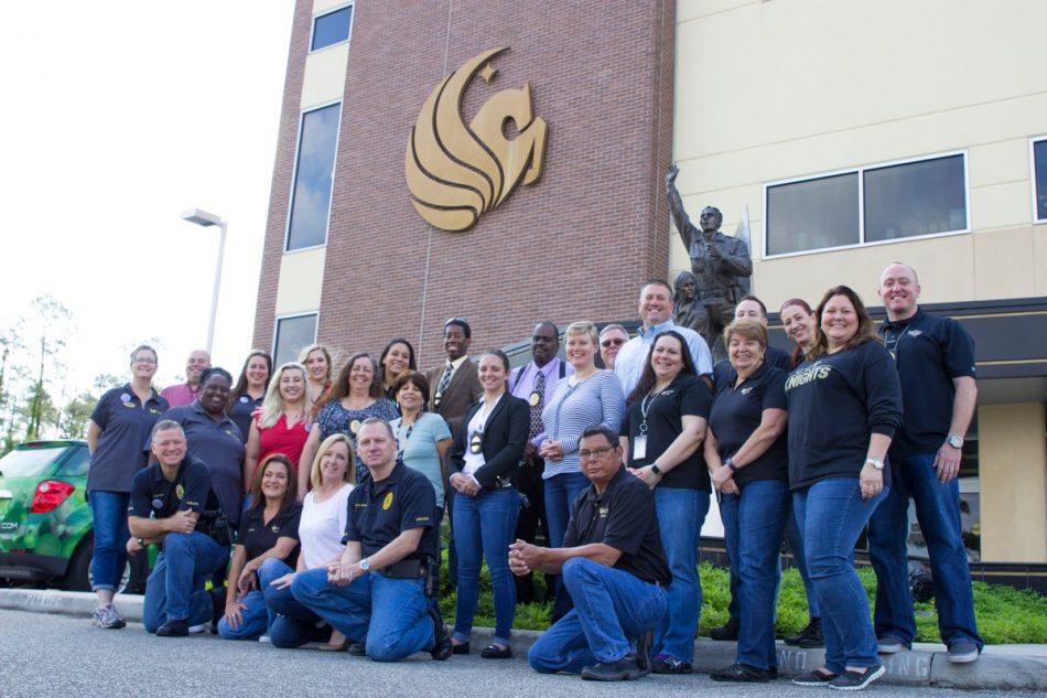 ucf police department staff and officers in front of police building with gold pegasus logo on brick wall