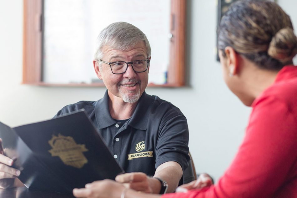 grey haired man with glasses and pegasus logo collared shirt talking to ethnic woman to his left