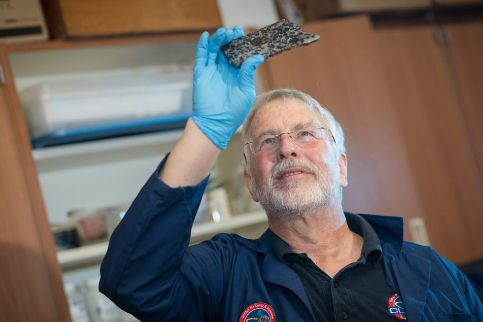 grey haired professor with glasses holding up a piece of asteroid with blue latex glove on his right hand