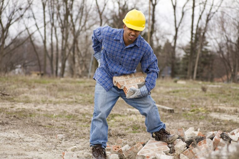 A man working on a construction site who has hurt his back. T
