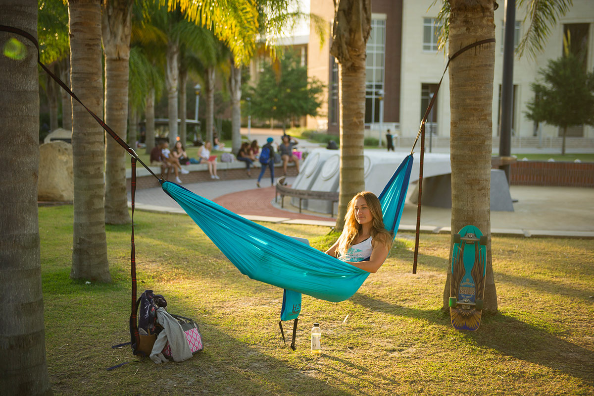 A white woman lays in a torquise hammock strung between two palm trees