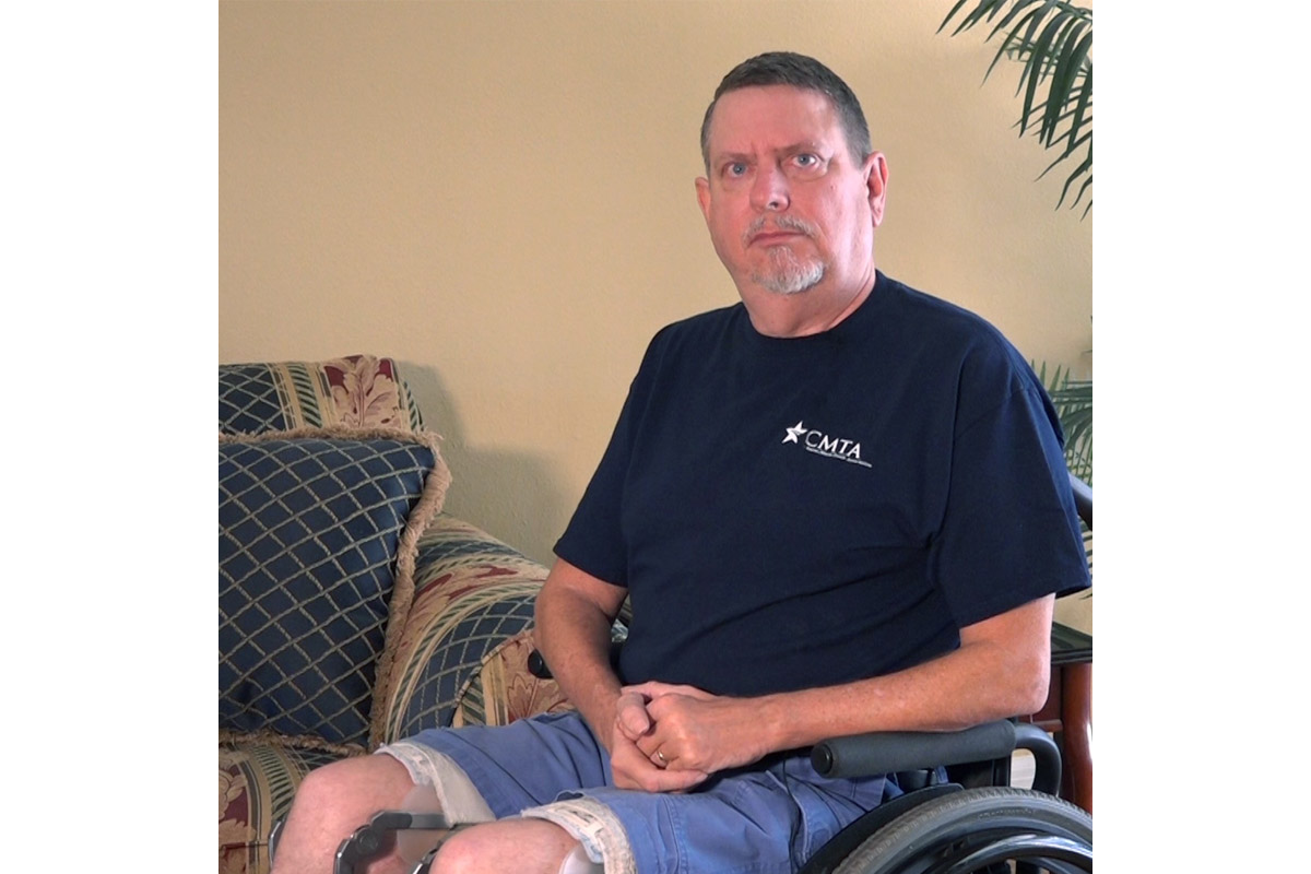 A white man in denim shorts and a navy blue t-shirt sits in a wheelchair, facing the camera.