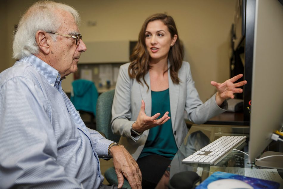 brunette woman in green shirt and grey blazer talking excitedly to an elderly man with white hair, glasses, and blue button down siting in front of a computer.