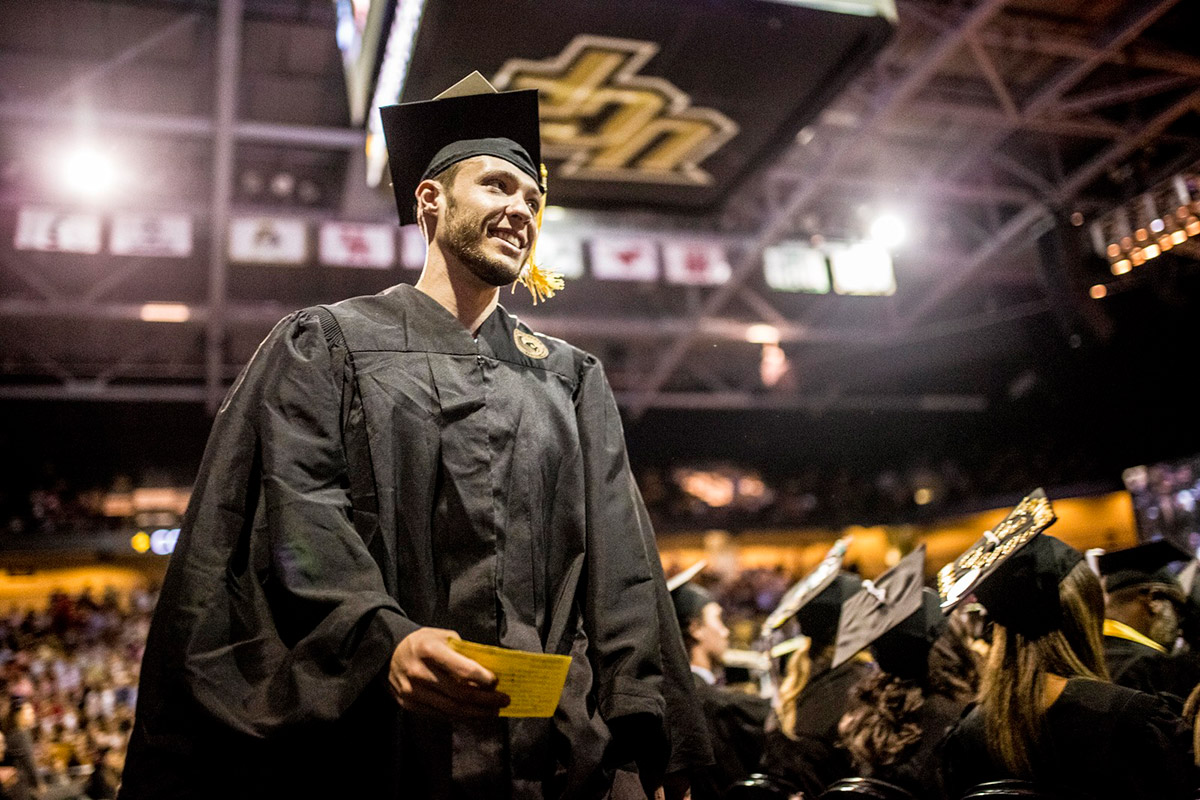 male ucf student in black cap and gown at graduation