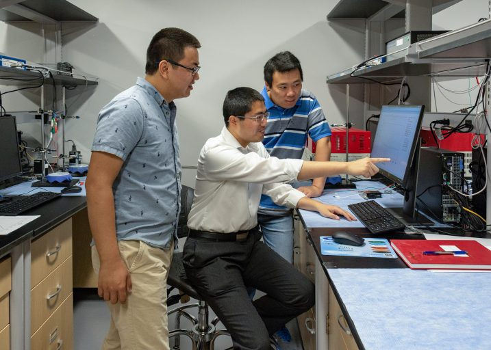 3 men in lab looking at a computer screen