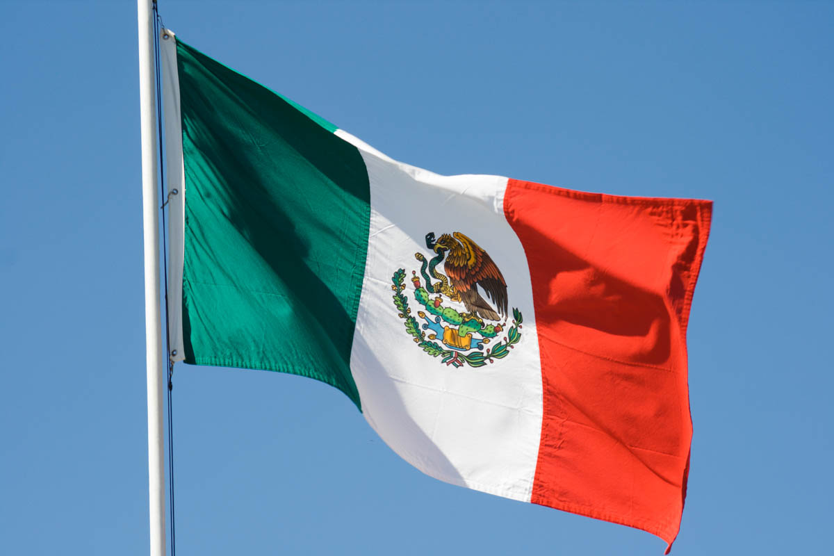 mexican flag on a flagpole waving in the wind with a blue sky in the background