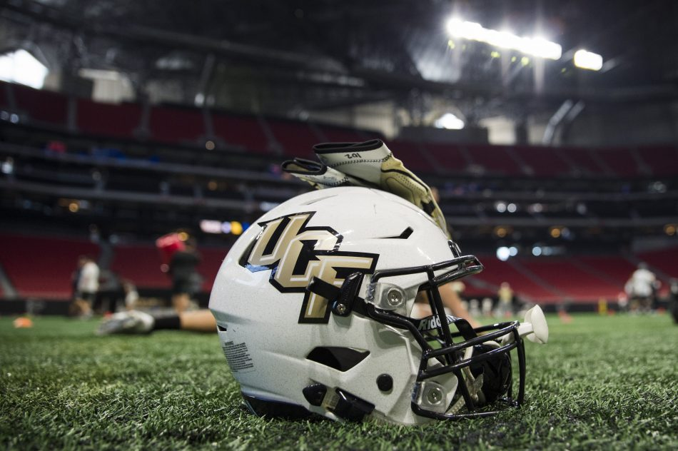 white football helmet with black and gold UCF written on the side. gold gloves placed on top of the helmet. the helmet is sitting on the grass of a football stadium while players practice in the background