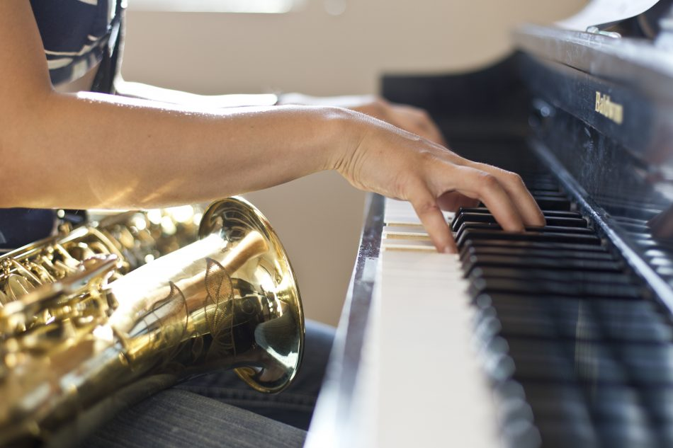 woman sitting, playing a piano with a saxaphone in her lap