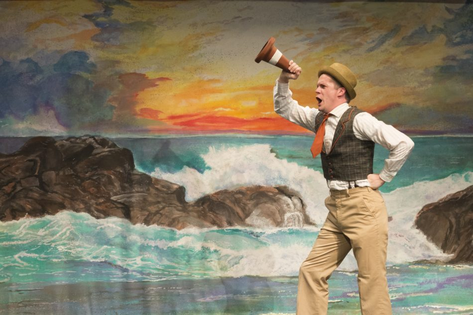 man in khaki pants, white long sleeve collared shirt, dark green vest, orange tie, wearing a tan hat is pretending to yell into a small traffic cone. standing in front of a mural of water hitting rocks in front of a sunset.
