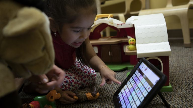 A child examines an app where words can be selected in sequential order and then the app verbally communicates that sentence for the user. Photo credit: University of New Mexico.