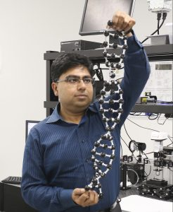 man with blue collared shirt, black hair, and glasses holding up a dna model