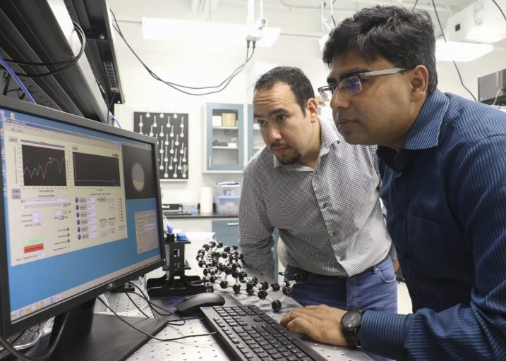 two men in a lab looking at computer screen, working on nanostructured optical sensor