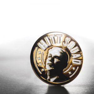 Image of gold pin that says Hitt Squad in white with a monochrome image of John Hitt.