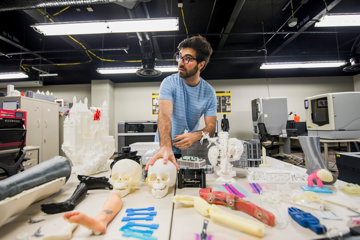 Fluvio Lobo, lead development engineer at the Prototype, Development and 3D Print Lab, showcases two skulls that were 3D printed at UCF to help surgeons at Nemours Children's Hospital plan the best way to remove a tumor from a patient. (Photo by Steven Diaz)
