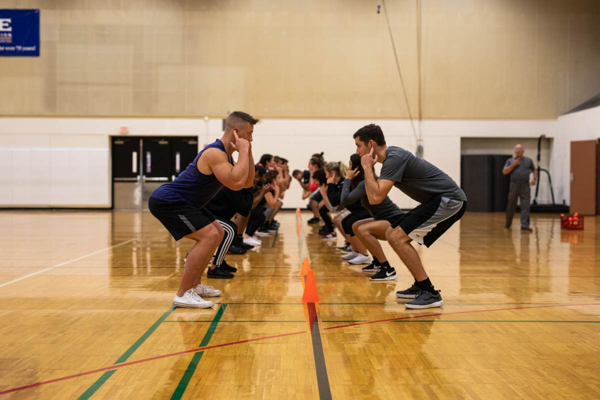 During a warm-up exercise, students test their reflexes by identifying pressure points on their bodies and competing against one another to see who grab a cone the fastest.