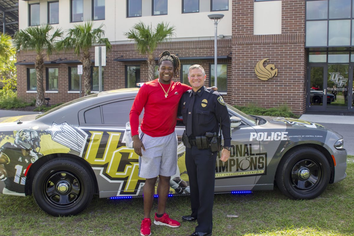 Carl Metzger greets Knights football player Shaquem Griffin, who stopped in April to see the police car commemorating the team's championship season. Metzger, chief deputy at the time, was named UCF's police chief in June, and Griffin now is a rookie linebacker in the Seattle Seahawks training camp. (Photo by Amanda Sellers '13)